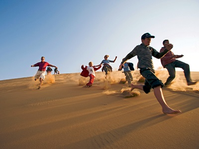 Namibia, Erongo Region, Swakopmund. A group of friends run down the steep face of a coastal dune kicking up sand.